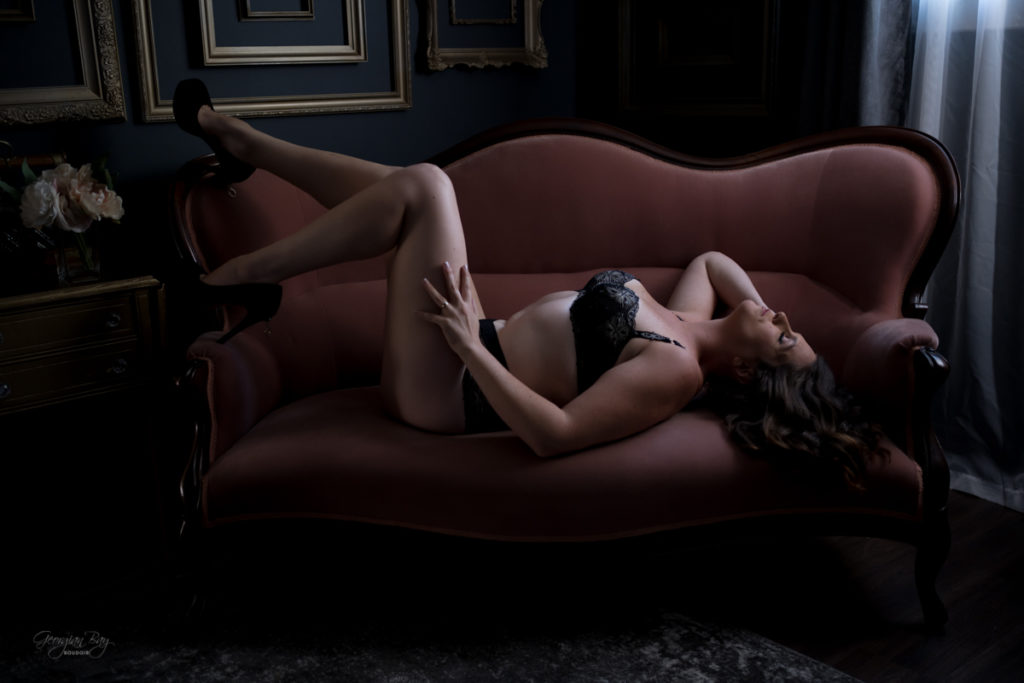 Dramatic boudoir photography with woman on pink couch